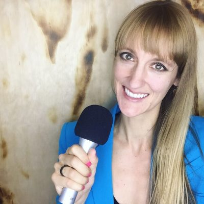 laura-headshot-with-microphone-wood-background